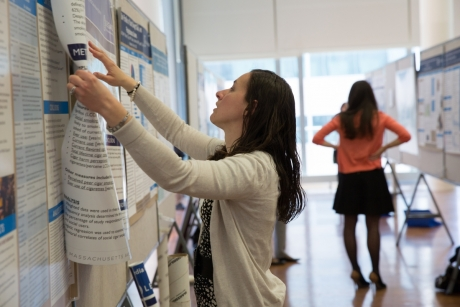 Research Days participant hangs her poster, 2015.
