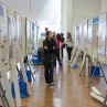 Guest walks through an aisle of research posters, 2015.